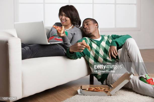teenage couple eating pizza and using laptop - teenagers only stock pictures, royalty-free photos & images