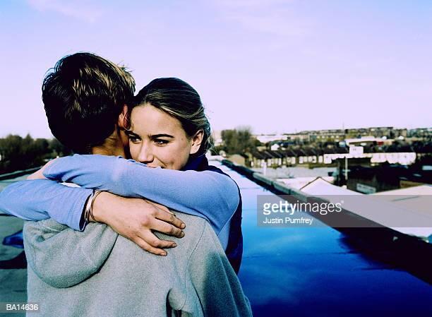 teenage couple (14-16) embracing on rooftop, view over boy's shoulder - 和解 ストックフォトと画像