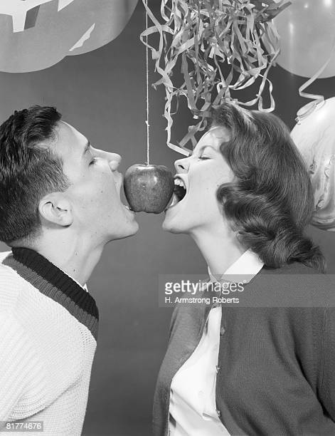 Teenage couple facing each other, attempting to bite apple hanging from ceiling by string, holding hands behind back.