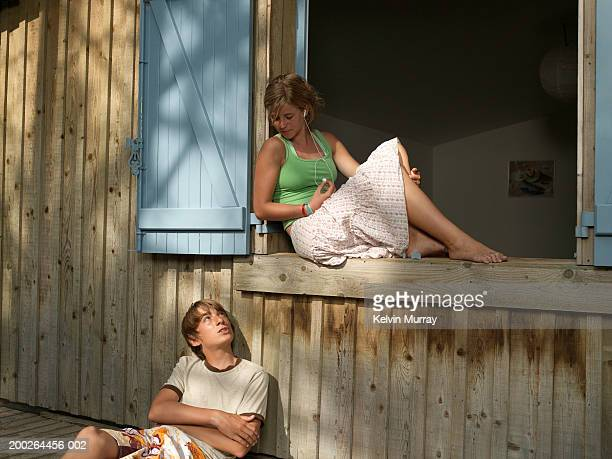 teenage couple (14-16), girl on window ledge looking down at boy - skirt stock pictures, royalty-free photos & images
