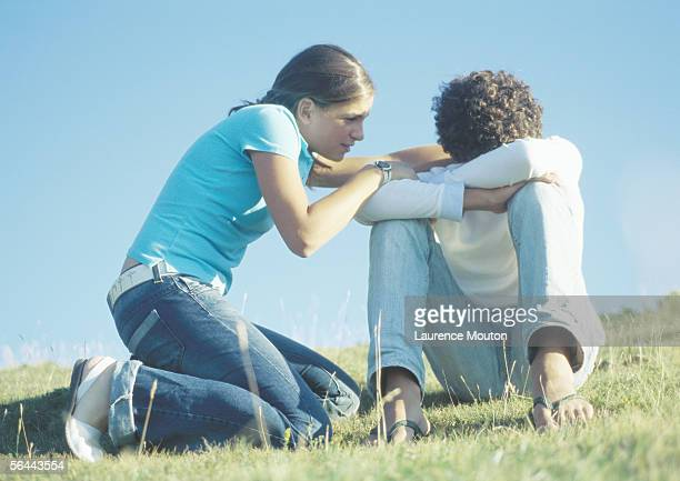 Teenage couple, girl trying to talk to boy with head down