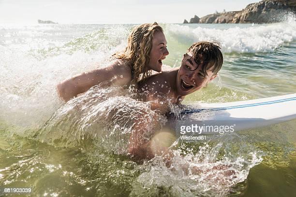 Teenage couple having fun on surfboard in the sea