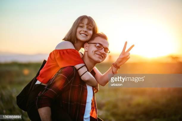 coppia adolescente che ha hun - portare a cavalluccio foto e immagini stock