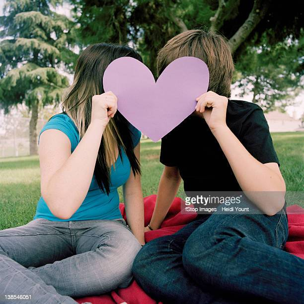 A teenage couple hiding behind a cut out heart