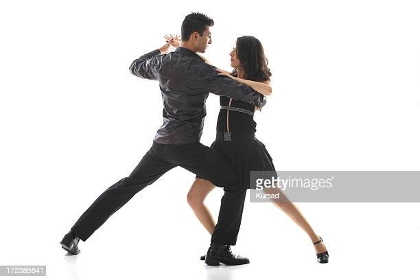 A teenage couple hold a salsa dancing pose