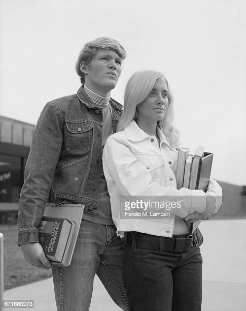 teenage couple holding books and looking away - {{relatedsearchurl(carousel.phrase)}} imagens e fotografias de stock
