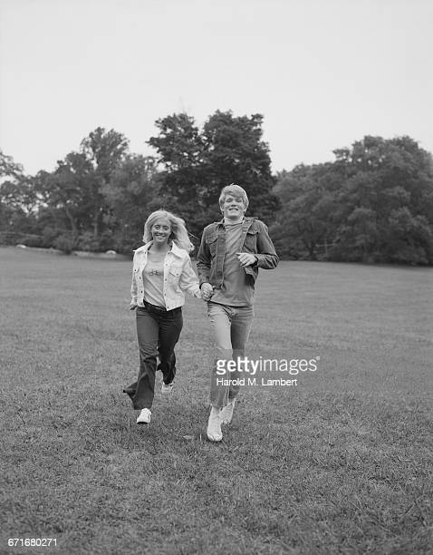 teenage couple holding hand and running through a lawn - {{ contactusnotification.cta }} stock pictures, royalty-free photos & images