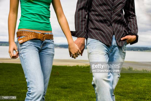Teenage couple holding hands and walking
