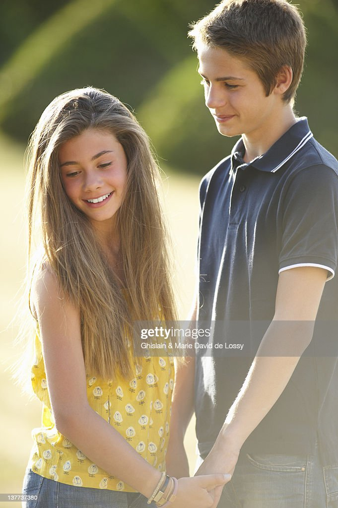 Teenage Couple Holding Hands Outdoors Stock Photo