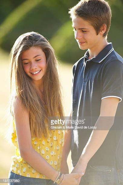 teenage couple holding hands outdoors - verliefd worden stockfoto's en -beelden