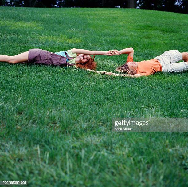 teenage couple (15-17) holding hands, rolling down hill - lying down photos et images de collection