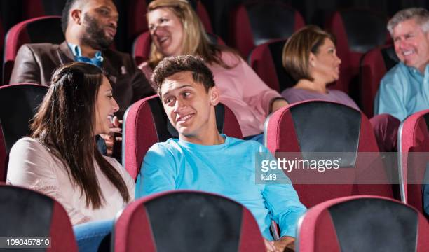 teenage couple in a movie theater talking - girlfriends films stock pictures, royalty-free photos & images