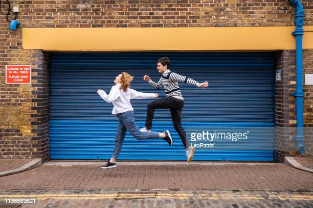 teenage couple jumping agains a garage door in london - mid air stock pictures, royalty-free photos & images