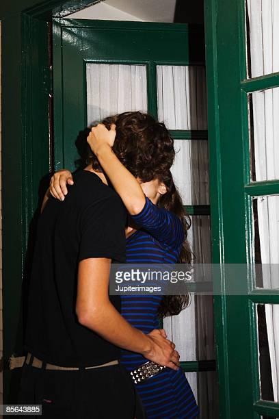 Teenage couple kissing in doorway