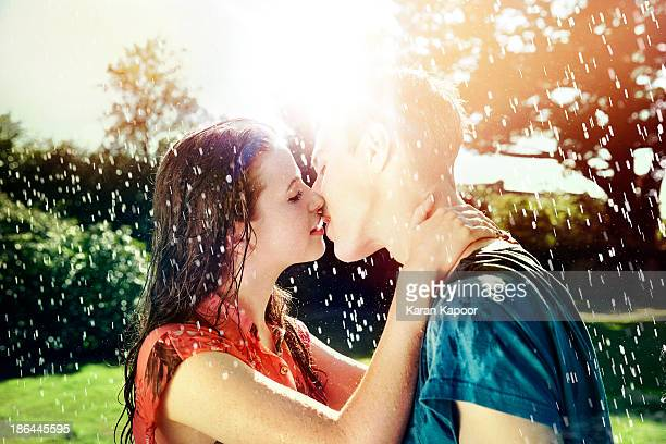 Teenage couple kissing in rain