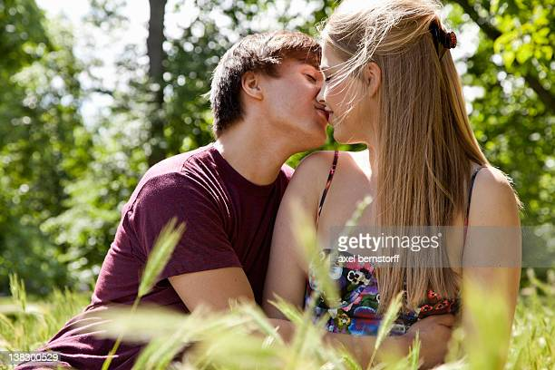 teenage couple kissing in tall grass - desire stock pictures, royalty-free photos & images