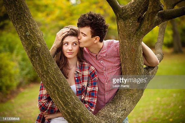 Teenage couple kissing in tree in park