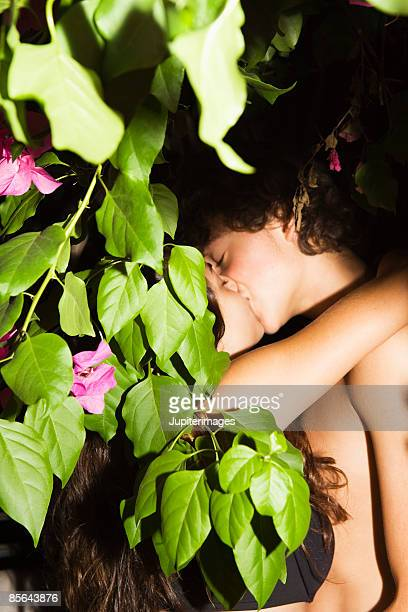 Teenage couple kissing under tree