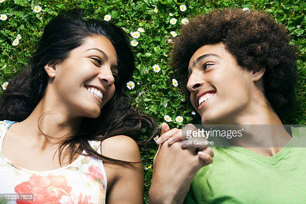 teenage couple laying in grass holding hands - petite amie photos et images de collection