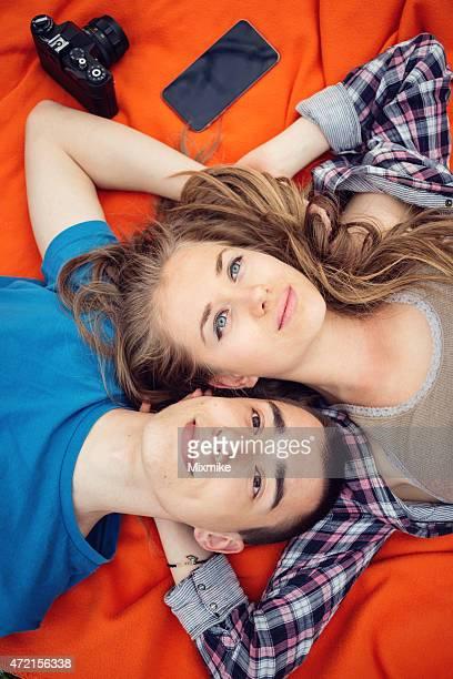 Jeune couple allongé sur une couverture picknik