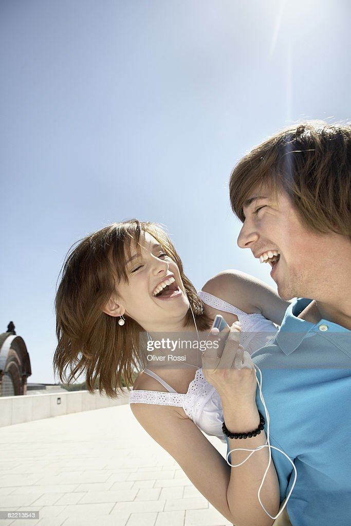 Teenage couple listening to MP3 player : Stock Photo