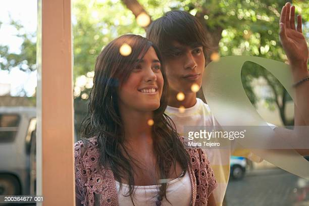 Teenage couple (16-18) looking in shop window, view through glass