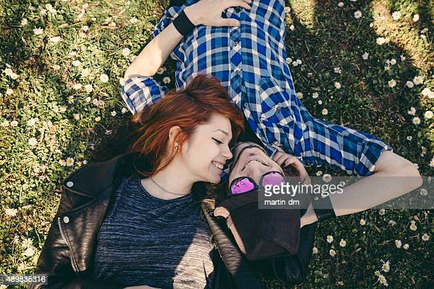 Teenage couple lying down in the grass