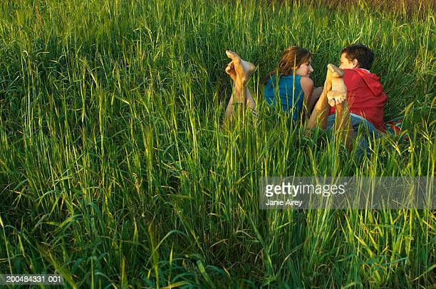 Teenage couple (17-19) lying in long grass, rear view