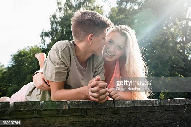 Teenage couple lying on a jetty at lake