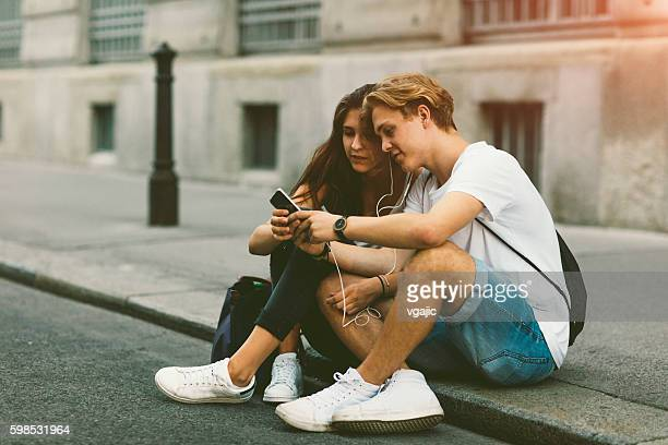 Teenage Couple Mobile Gaming Outdoors.