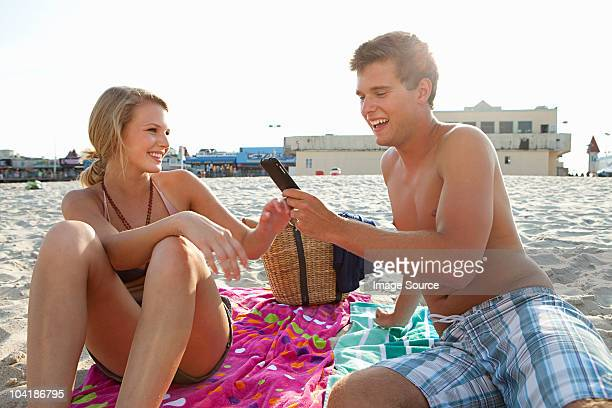 Teenage couple on the beach with cellphone