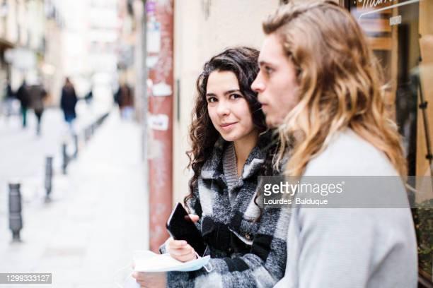teenage couple on the street - heteroseksueel koppel stockfoto's en -beelden
