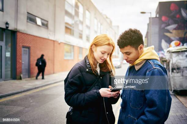 Teenage couple or friends looking at a phone together in the street