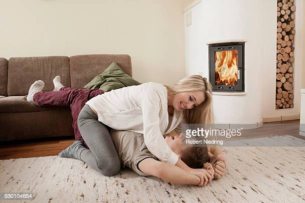 Teenage couple playfighting on carpet in front of fireside