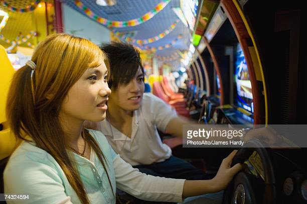 Teenage couple playing games in video arcade