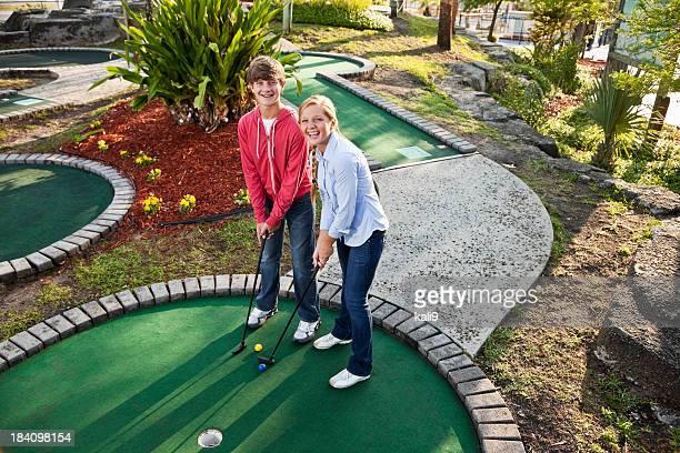 Teenage couple playing miniature golf