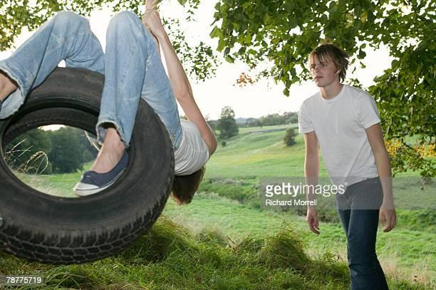 teenage couple playing on tire swing - partire bildbanksfoton och bilder