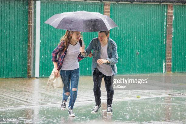 teenage couple run in the rain - romantic rainy day stock photos and pictures