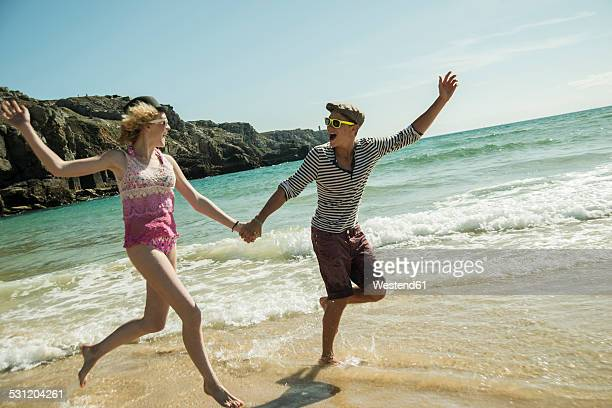 Teenage couple running hand in hand at waterside of the beach