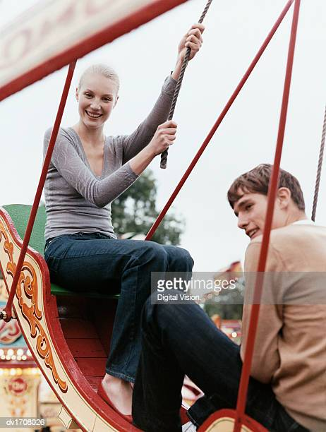 teenage couple sit face to face in a swing boat in a fairground - ポセイドン ストックフォトと画像