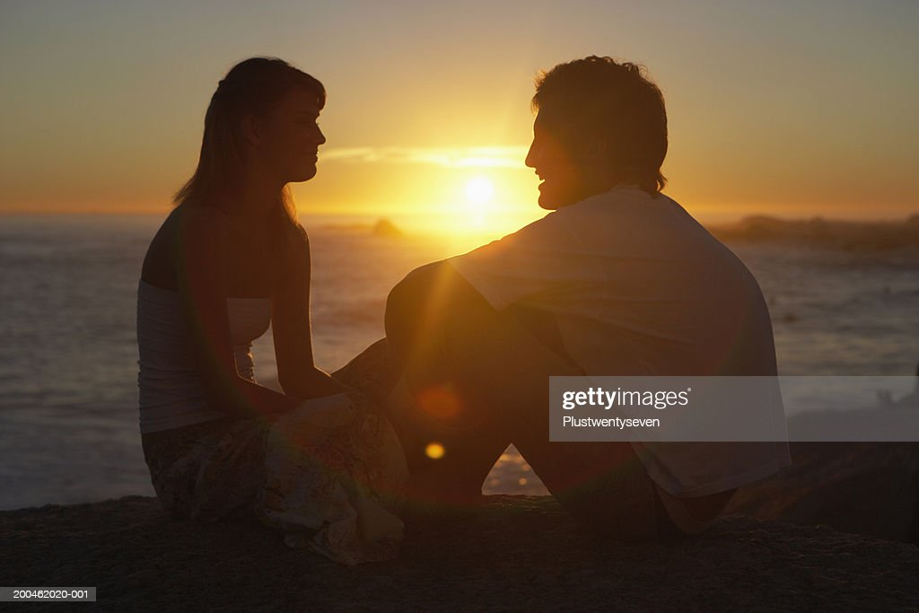 Teenage couple (15-19) sitting face to face on beach, sunset : Stock Photo