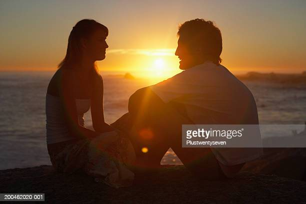 teenage couple (15-19) sitting face to face on beach, sunset - teenage couple stock photos and pictures