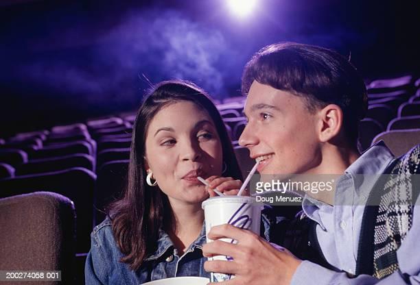 Teenage couple (16-17) sitting in cinema with popcorn, sharing soda