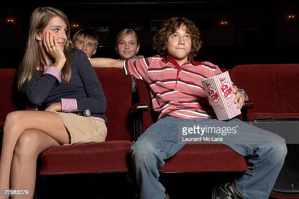 teenage couple sitting in movie theatre auditorium - divergent film stock photos and pictures
