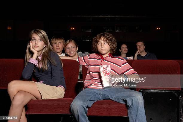 Teenage couple sitting in movie theatre auditorium