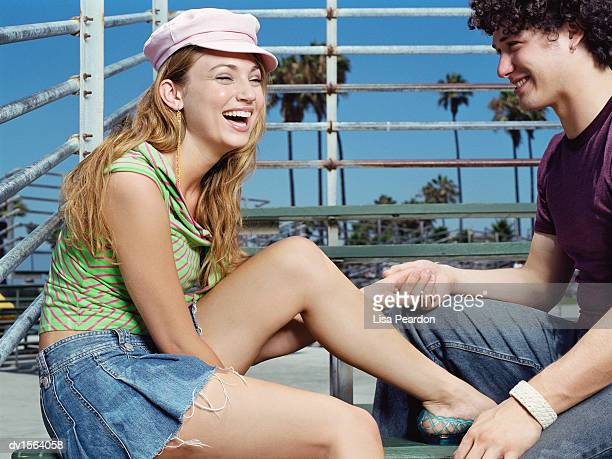 teenage couple sitting on a bench laughing - short skirt teens stock photos and pictures