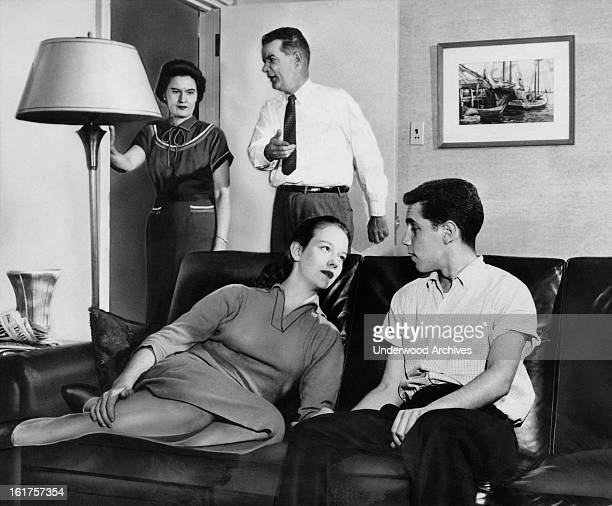 A teenage couple sitting on a couch gaze into each other's eyes while the parents show their disapproval Massachusetts September 1958