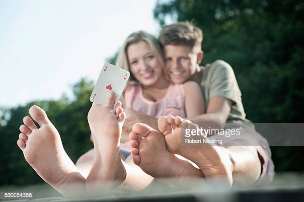 Teenage couple sitting on a jetty at lake, girl holding an ace between her toes