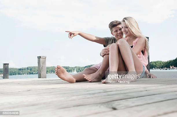 teenage couple sitting on a jetty at lake - teen soles stock photos and pictures