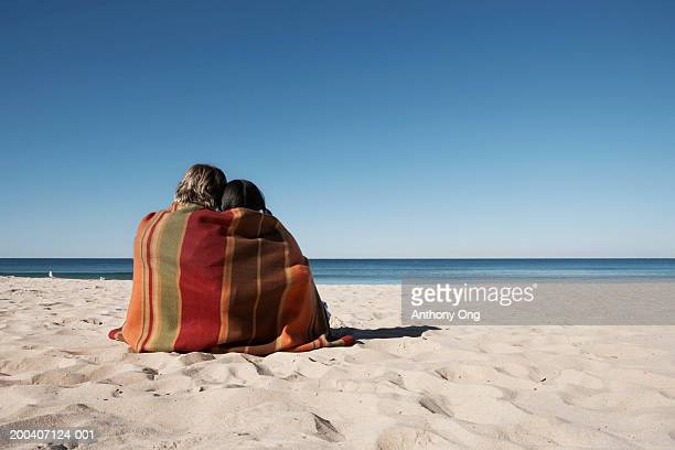 Teenage couple (16-18) sitting on beach wrapped in blanket, rear view